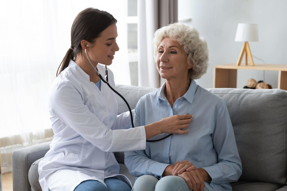 Young woman doctor holding stethoscope examining senior grandma patient