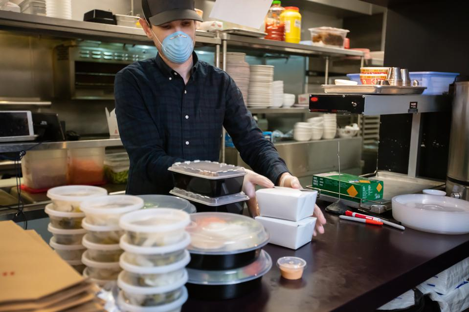 Masked and Gloved Restauranteur Packaging Food for Delivery During Covid-19 Outbreak