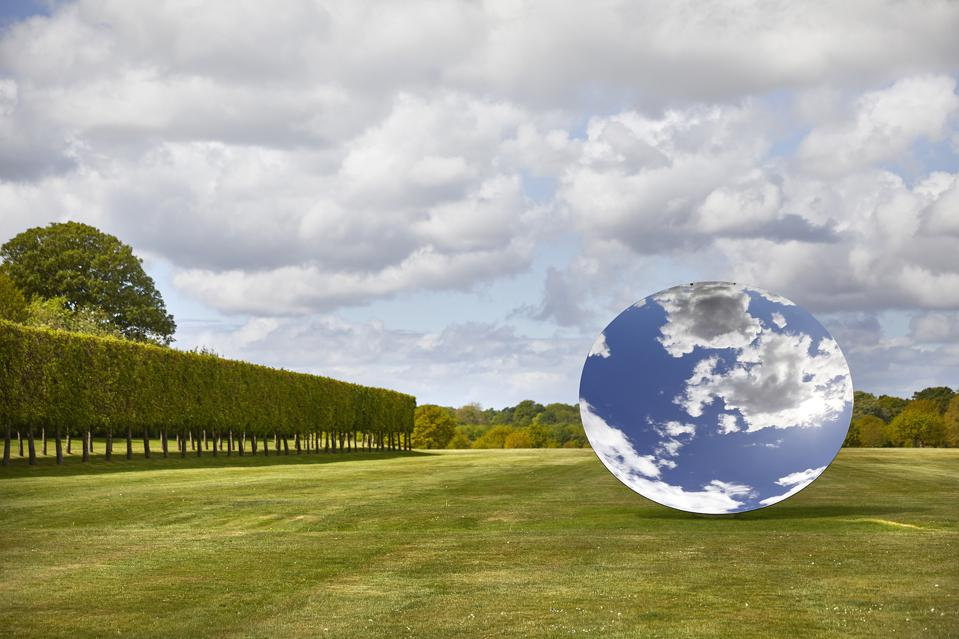An Anish Kapoor exhibition piece in countryside.