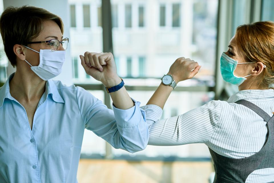 Business colleagues with face masks greeting with elbows during coronavirus pandemic.
