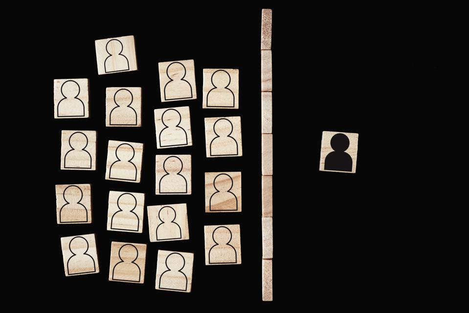 Concept of racism and misunderstanding between people, prejudice and discrimination. Wooden block with a white people figures and one with black man