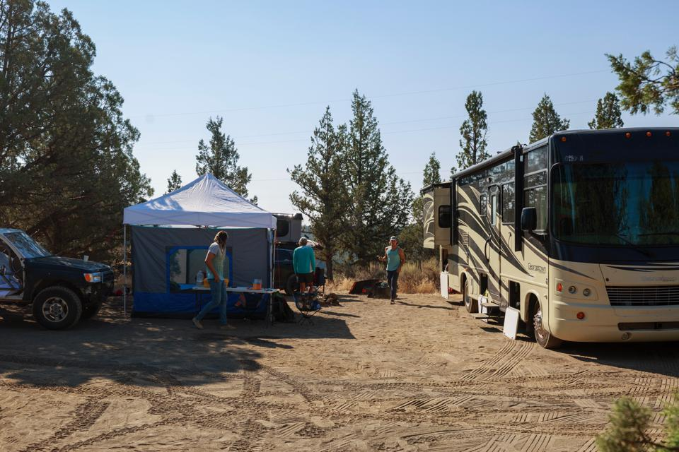 A campsite included a tent, RV and off-road vehicles.