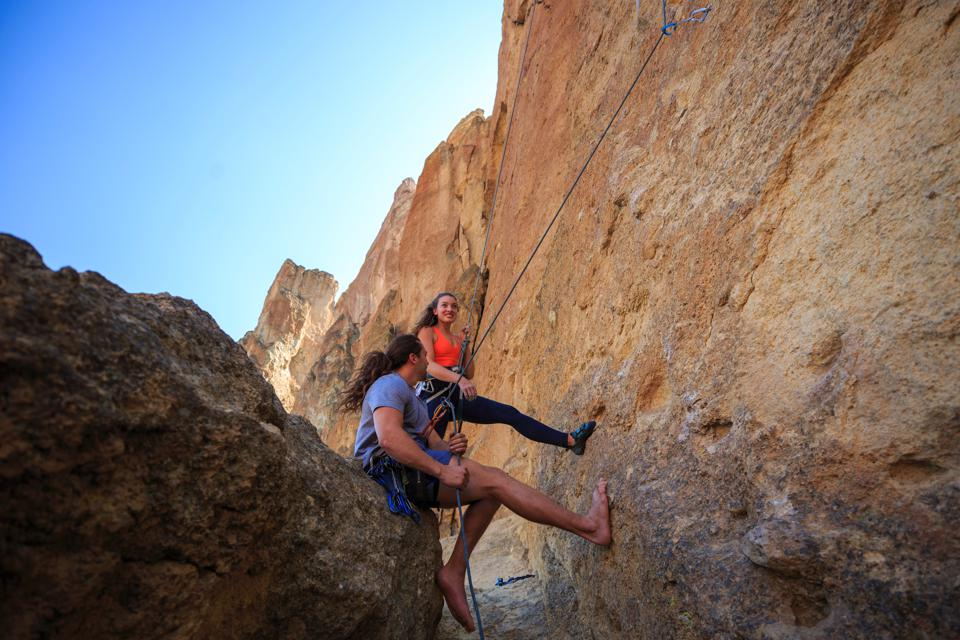 Two rock climbers prepare for an ascent in on desert sandstone.