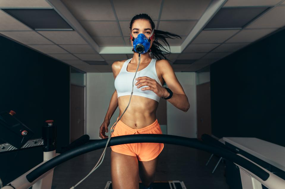 Athlete with mask running on treadmill.