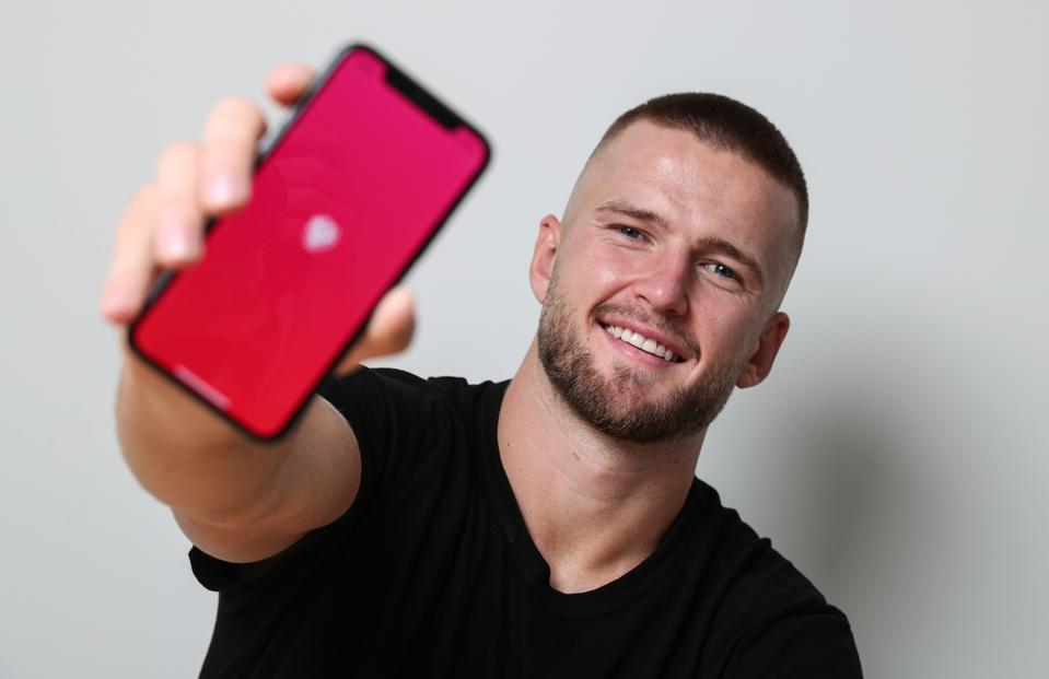 Eric Dier holds up a phone with his app Spotlas loading on the screen