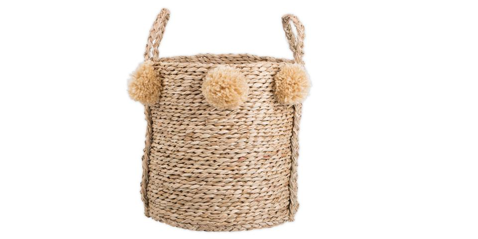 a seagrass basket with pom poms