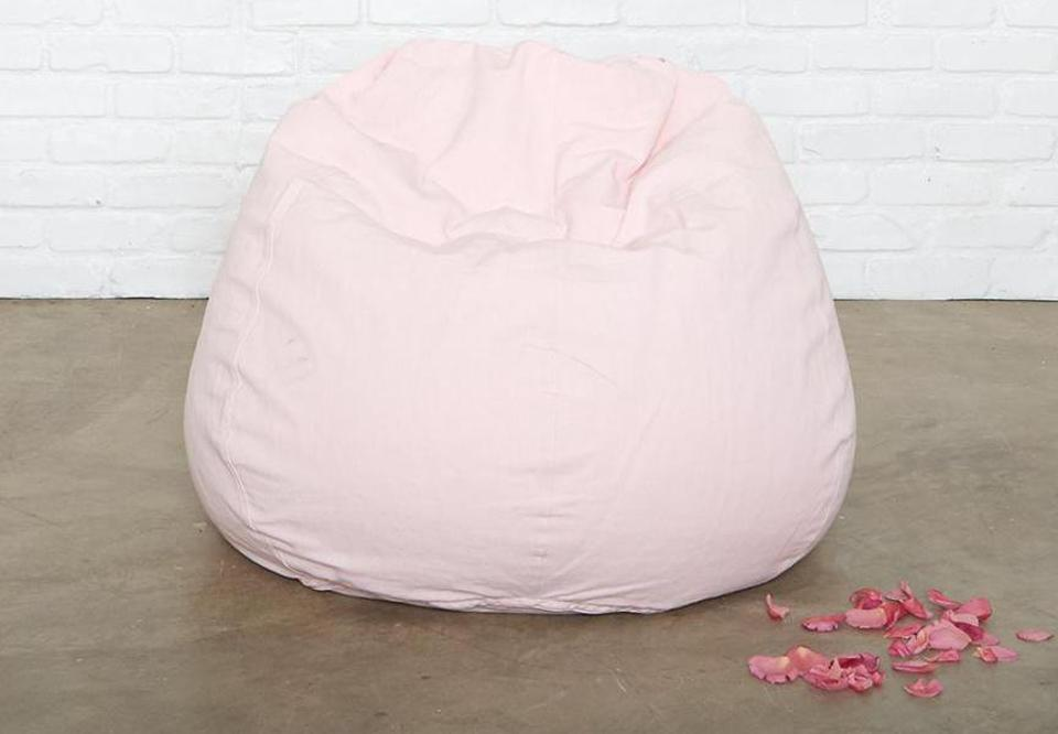 A pink beanbag chair on a concrete floor with a brick wall and petals
