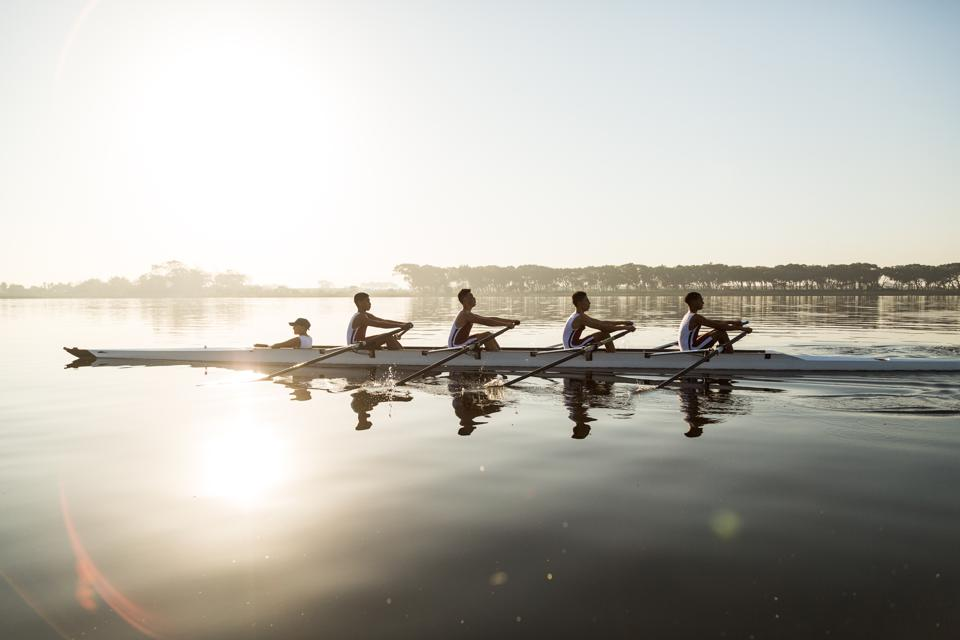 Mixed race rowing team training on a lake at dawn