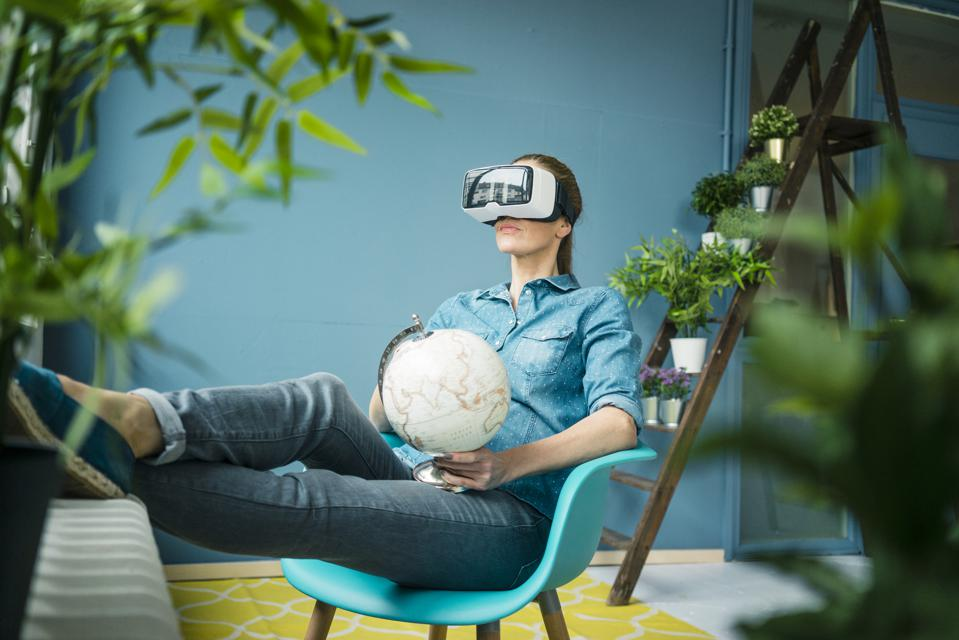 Beautiful woman sitting in her home, decorated with plants, holding globe, wearing VR glasses