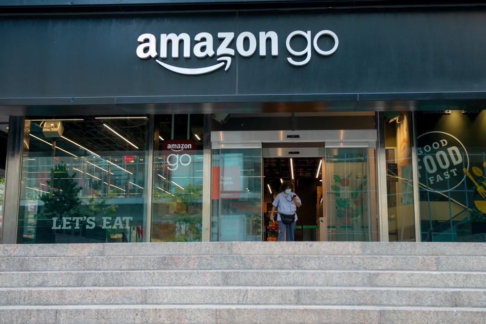 A woman wearing a mask walks out of an Amazon Go store as New York City