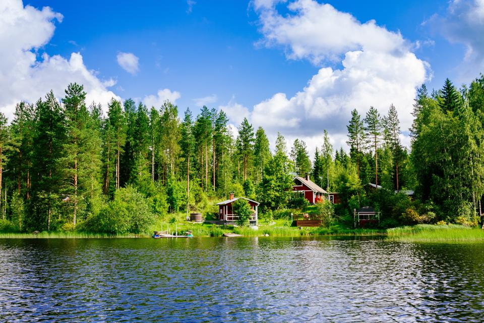 A traditional Finnish wooden cottage with a sauna and a barn on the lake shore.