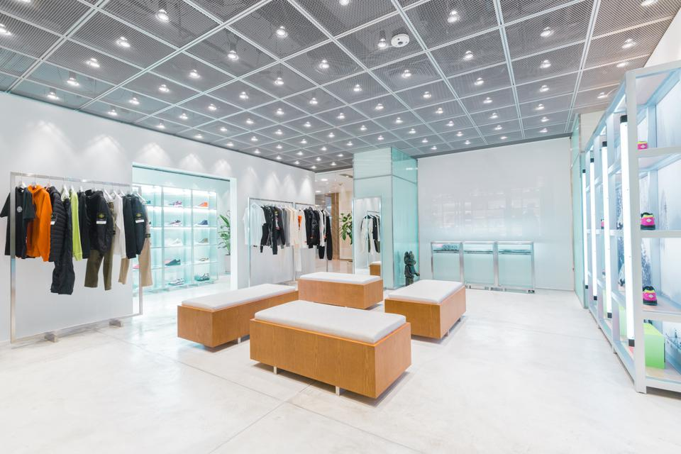 The minimalistic store design emphasizes HBX's curated merchandise and sneaker wall as the core focus of the retail experience.