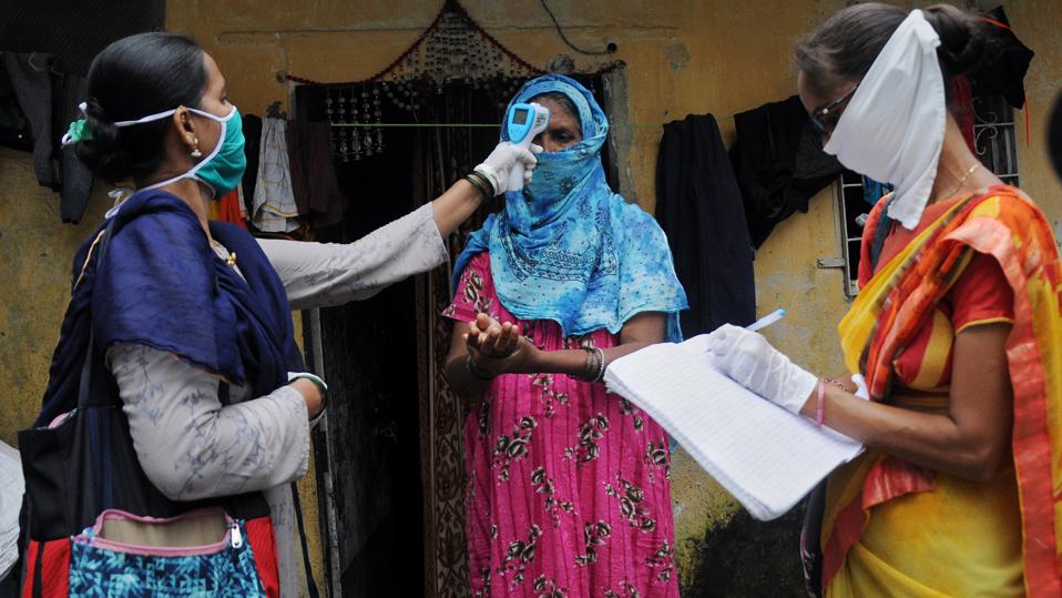 Community healthcare volunteer checks temperature of a woman...