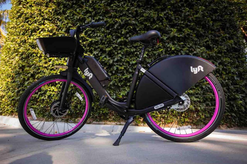 A black bicycle with magenta walled tires.