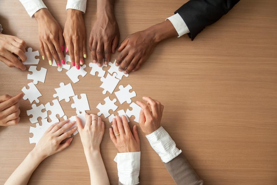 Hands of multi-ethnic business team assembling jigsaw puzzle, top view