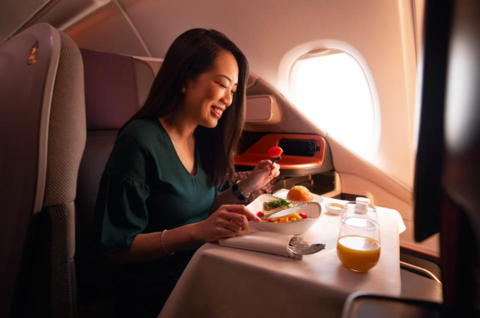 A woman enjoying a business class meal on Singapore Airlines