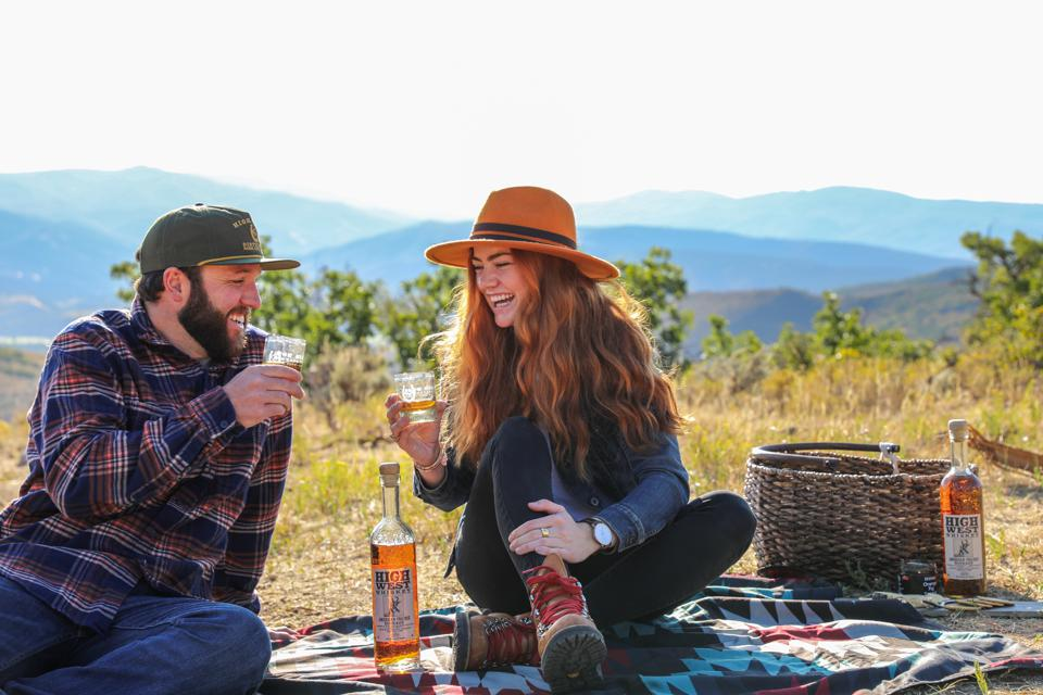 guy and girl drinking whiskey outdoors on a blanket