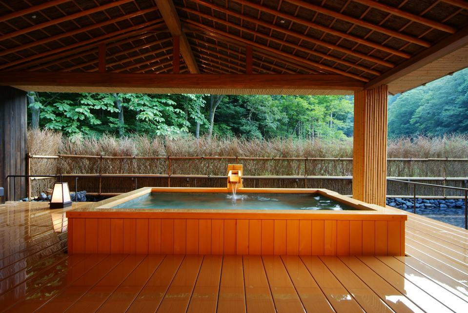 A private onsen bath in wooden tub at Nishimuraya Hotel Shogetsutei in Kinosaki, Japan.