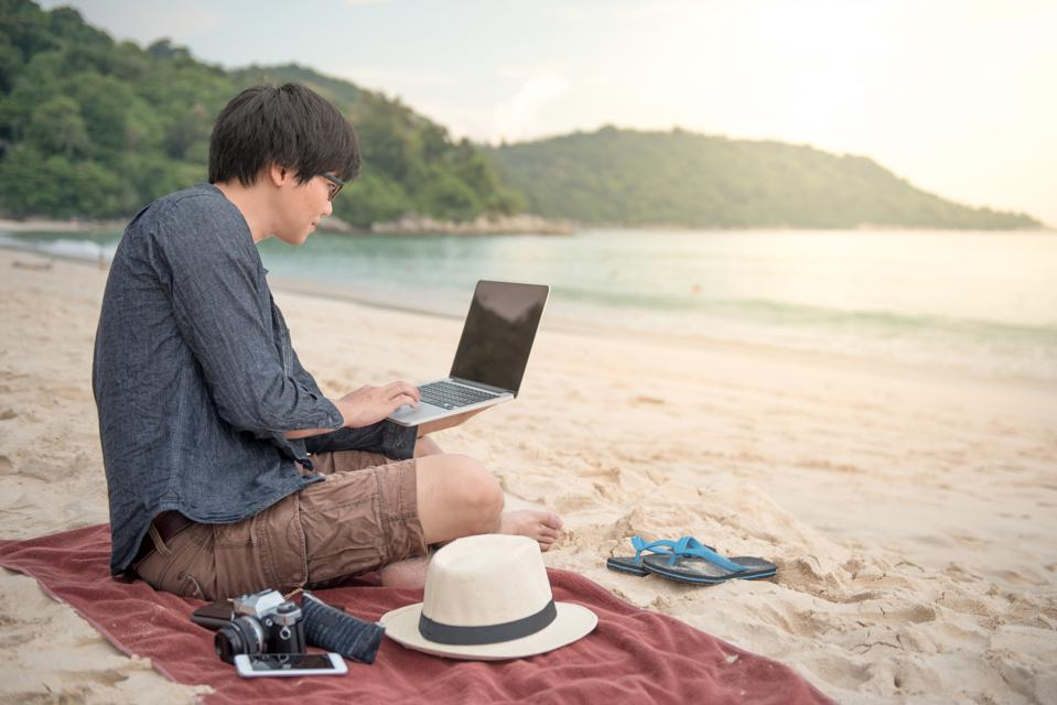 Young Asian man working with laptop computer on tropical beach