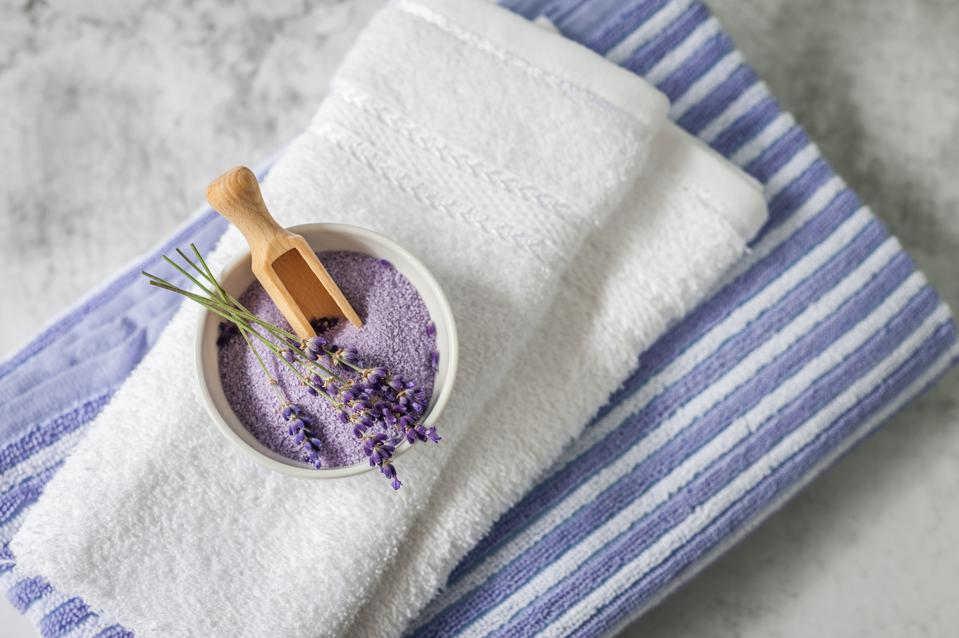 Lavender SPA. Lavender flowers and bath salt in bowl on towels background.