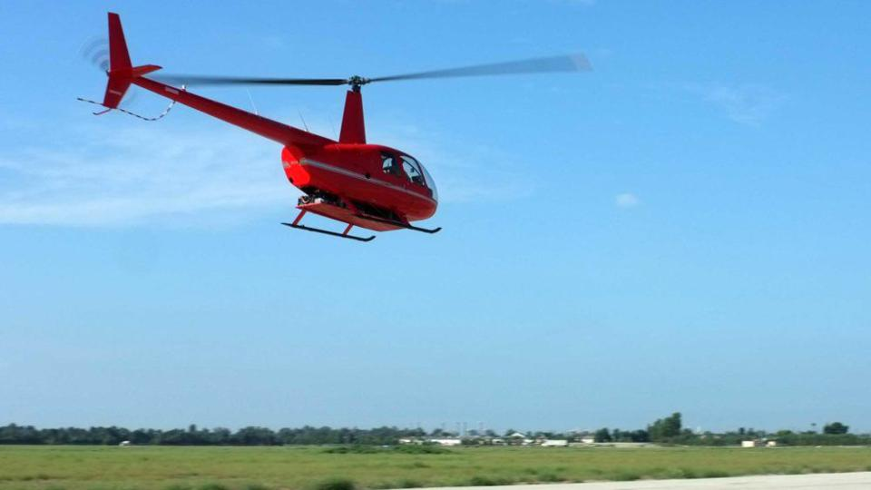 The Tier 1 Engineering electrified version of the Robinson R44 lifts off from a taxiway.