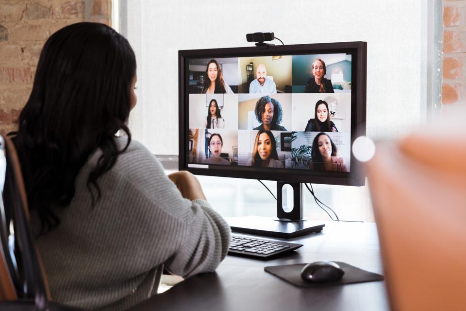 Businesswoman meets with colleagues during virtual staff meeting