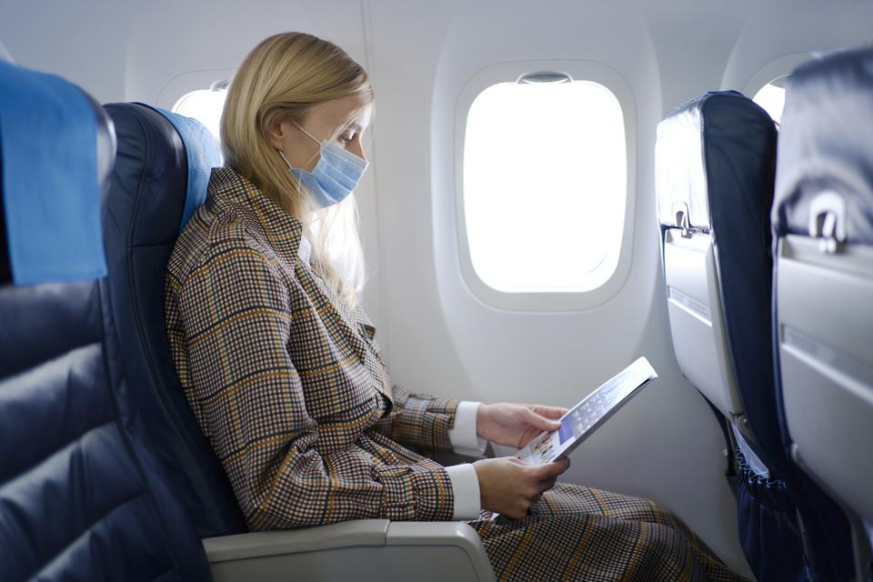 Woman wearing mask inside airplane