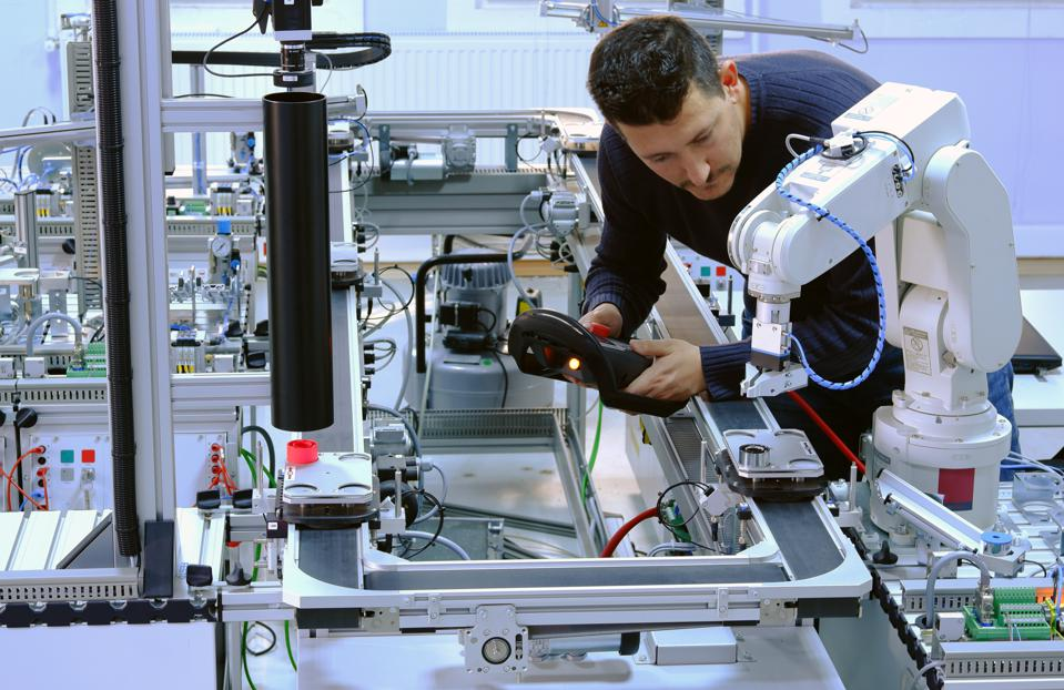 Industry 4.0 concept: An engineer is programming robotic arm
