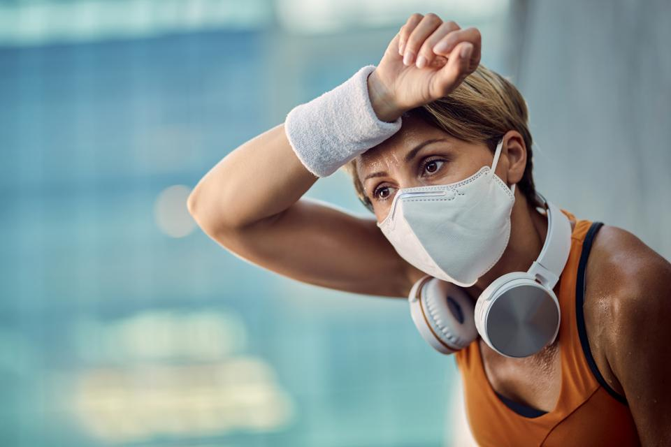 Runner wiping sweat from her forehead.