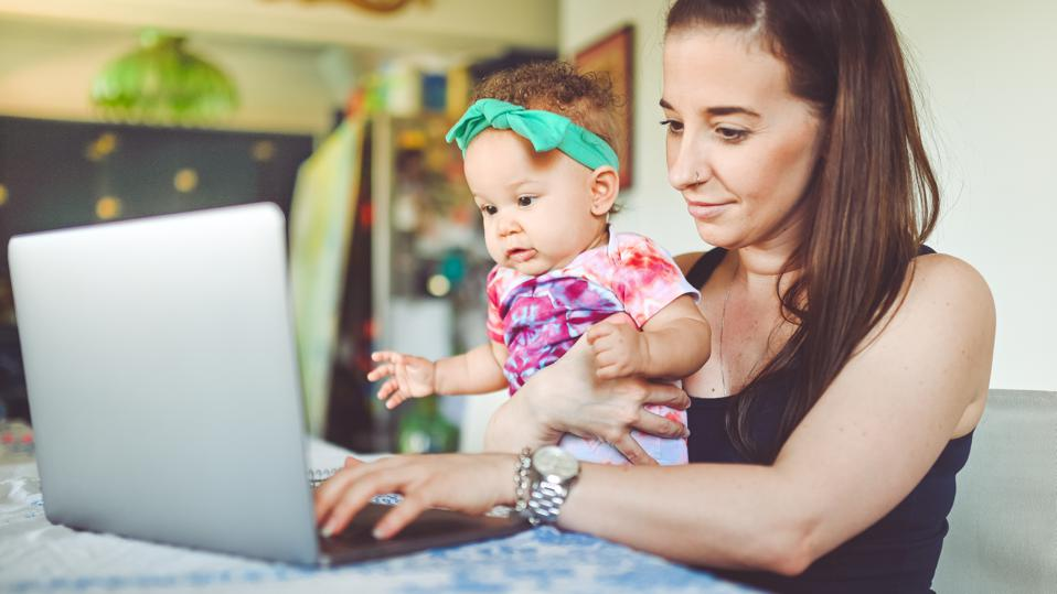Mother and baby sit in front of a laptop at home, working, video chat or telemedicine