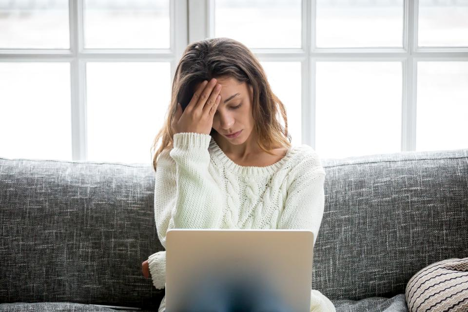 Frustrated woman worried about problem sitting on sofa with laptop