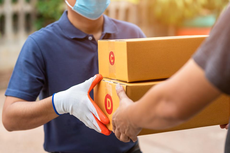 Delivery asian man holding cardboard boxes in medical rubber gloves and mask. Online shopping and Express delivery, or ecommerce. concept prevent the spread of germs and avoid infections Covid-19