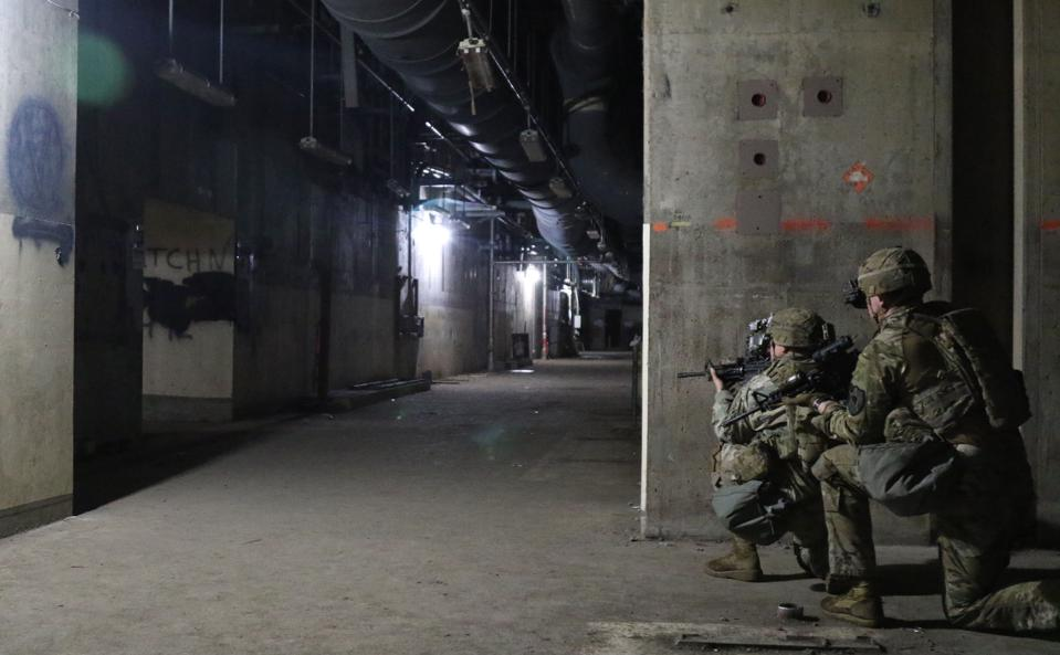 Two soldiers hold rifles at the ready in an underground corridor.