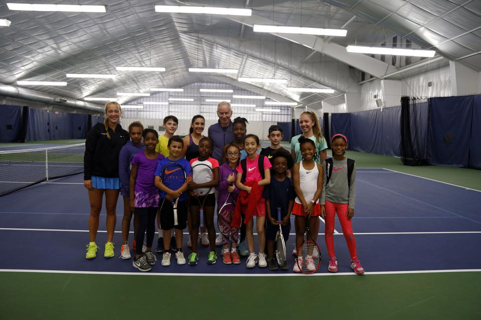 John McEnroe on the court with students.