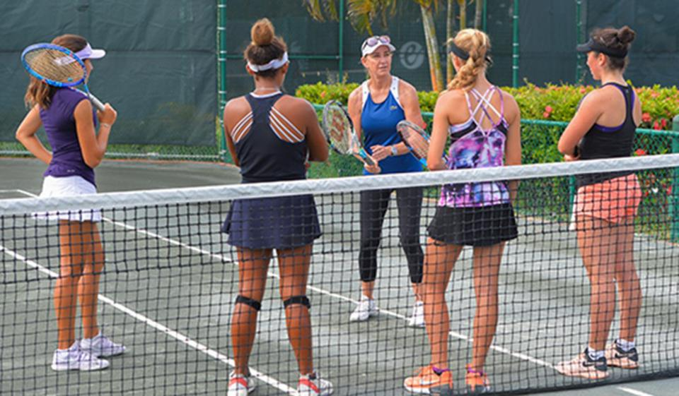 Chris Evert working with students on a court.