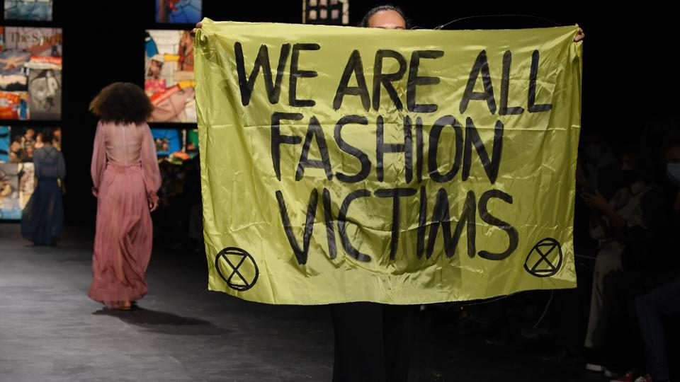 Extinction Rebellion protestor on Dior runway with flag reading We are all fashion victims