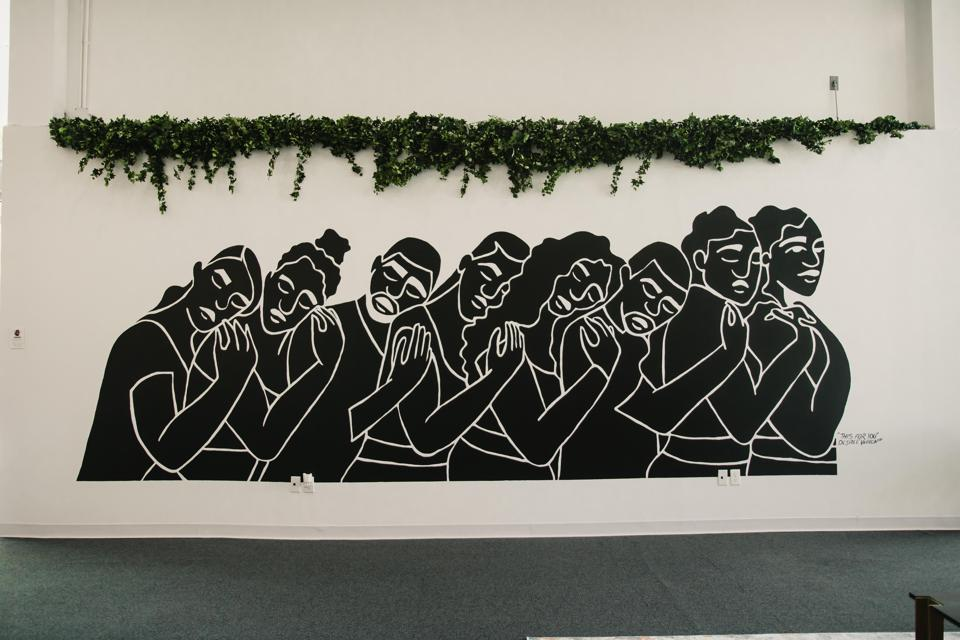 Mural image of people in a line in black embracing one another