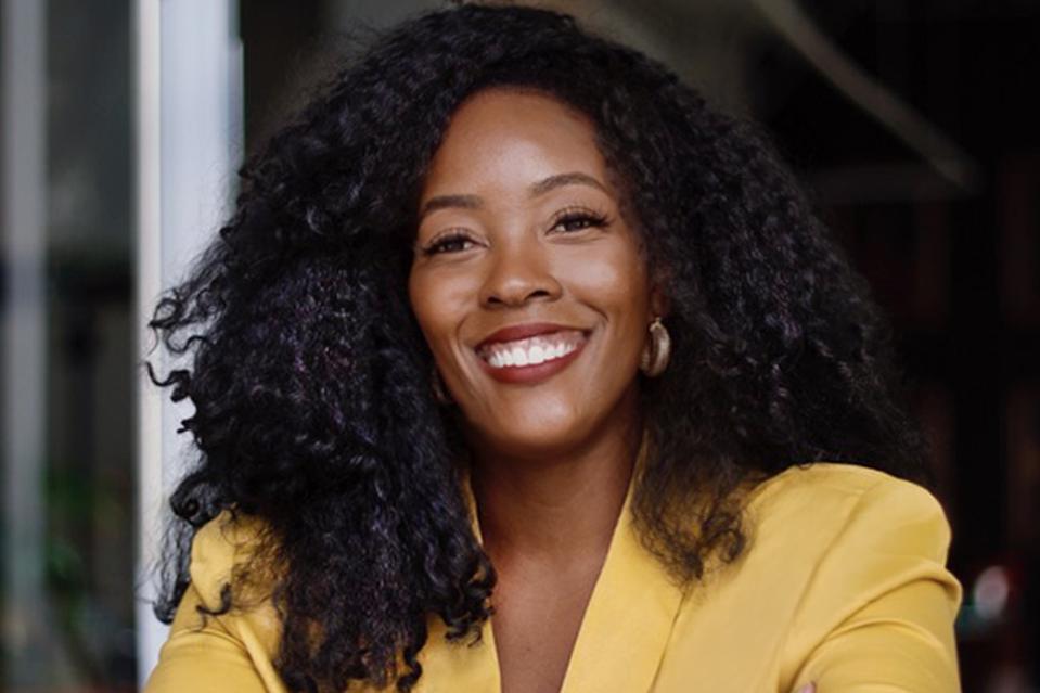 Headshot of Cimone Key, international brand consultant, wearing yellow.