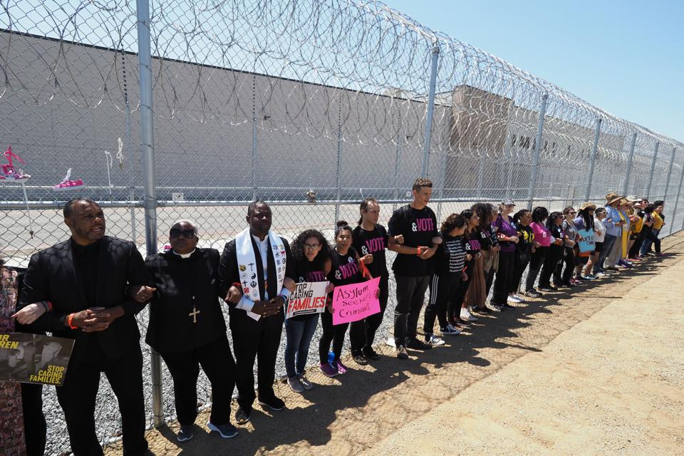 Protestors link arms after tying children's shoes and keys on the fence outside the Otay Mesa  Detention Center