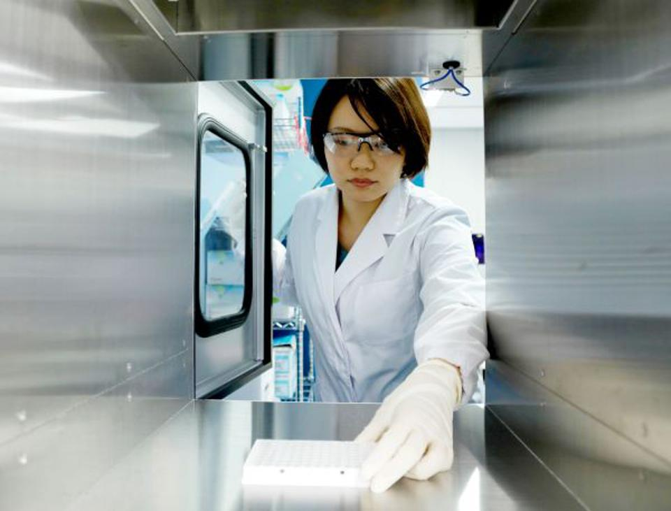 A technician prepares samples at PFDeNA's lab in Tokyo