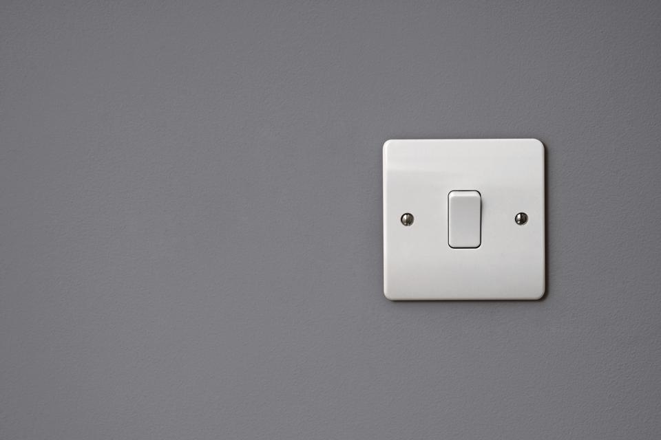Close-up of white square light switch on the wall