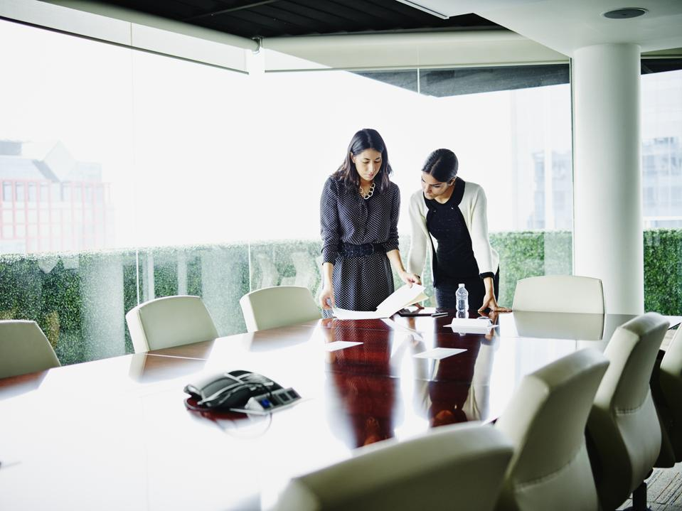 Two female business executives reviewing documents