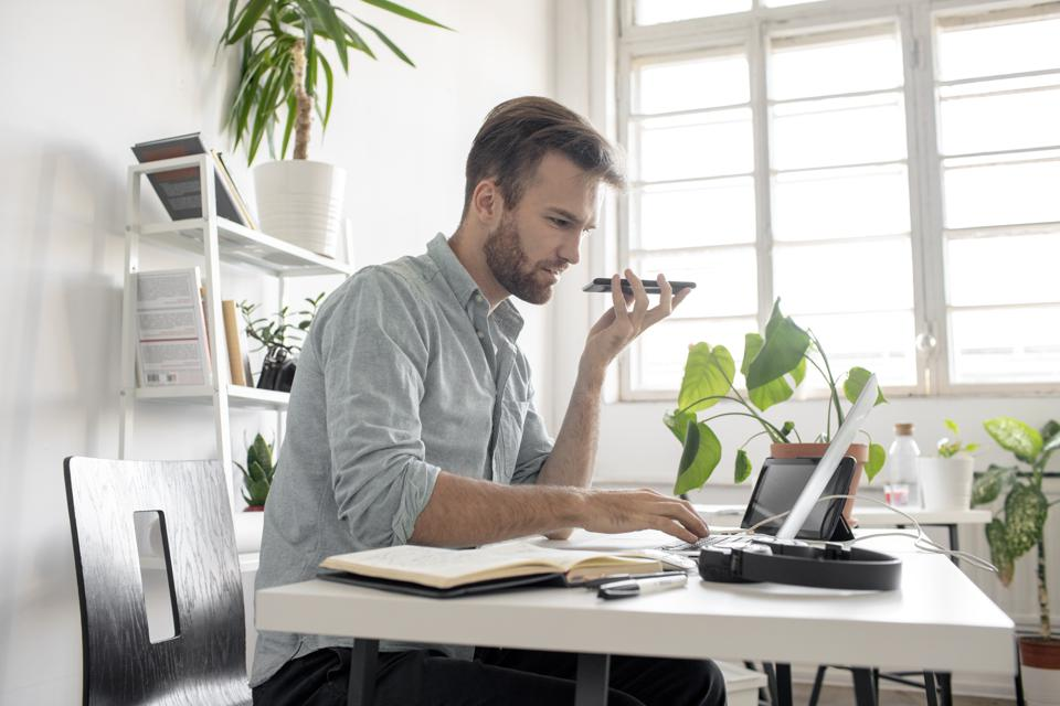 Man using smartphone and laptop at desk in office