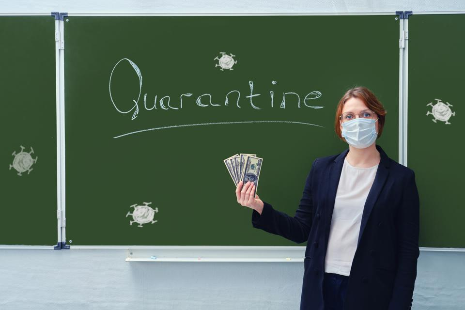 A school teacher in a medical mask holds us dollars at the blackboard with the words ″Quarantine″. The concept of money problems during the coronavirus epidemic