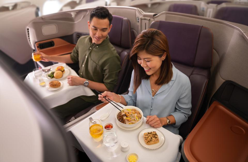Man and woman eating business class meal in airline cabin.