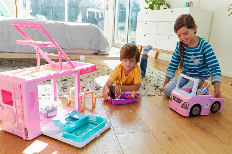 Young boy and girl role playing with Barbie dolls and vehicles