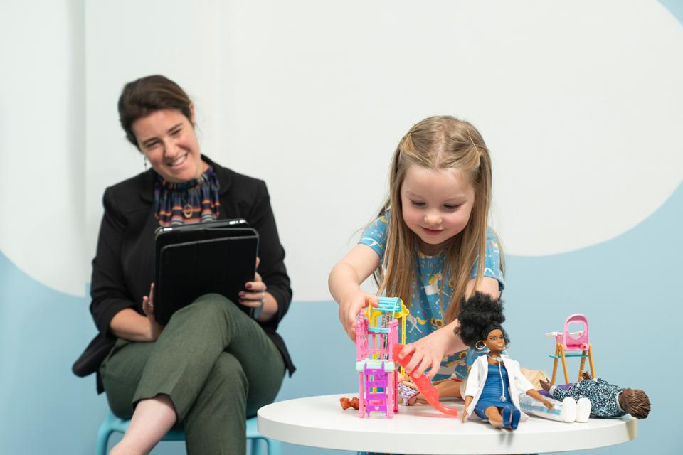 Female academic from Cardiff University observing a young girl playing with Barbie dolls during the research