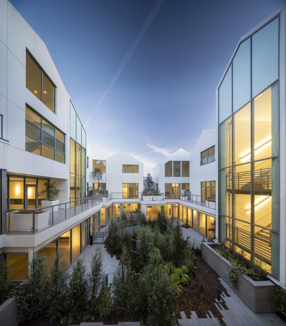 The open-air inner courtyard of Gardenhouse is installed with a dense canopy of trees, native plantings and a water feature flowing from the second floor to the ground-floor entrance lobby
