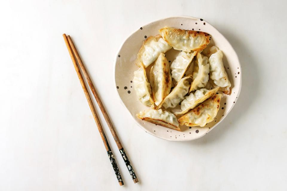Fried asian dumplings Gyozas potstickers in white ceramic plate served with chopsticks and soy spring onion sauce over white marble background. Flat lay. space. Asian dinner