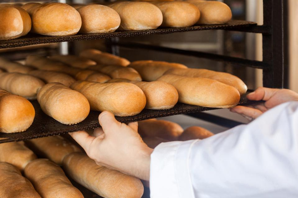 Closeup of hands of professional chef man in white uniform standing near shelves full with fresh bread and pulling baking tray for checking quality